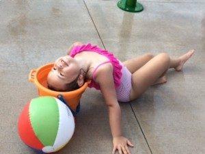 splash park little girl with head in bucket